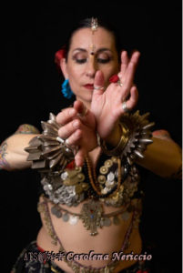 トライバル(Tribal)とは「民族的な」という意味を持つ英語で、ベリーダンスにおけるトライバルスタイルは民族舞踊にインスパイアされたダンスといわれており、筋肉のアイソレーション(体の一部位を独立させて動かすこと)や流れるようなムーブメントにより視覚的に人を惹き付けます。 1960年代にアメリカ西海岸ではじまり、それまで主流だったオリエンタル(キャバレー)スタイルとは一線を画した表情、動き、衣装で年々愛好家を増やしています。 アメリカントライバルスタイル(ATS) 1980年代後半に『FatChanceBellyDance』代表のキャロリーナ・ネリッキオが誕生させたアメリカントライバルスタイル(ATS)は北部インドや中東地域、アフリカをはじめ、ありとあらゆる文化を融合させたスタイルともいわれ、息の合ったグループでのパフォーマンスが特徴です。